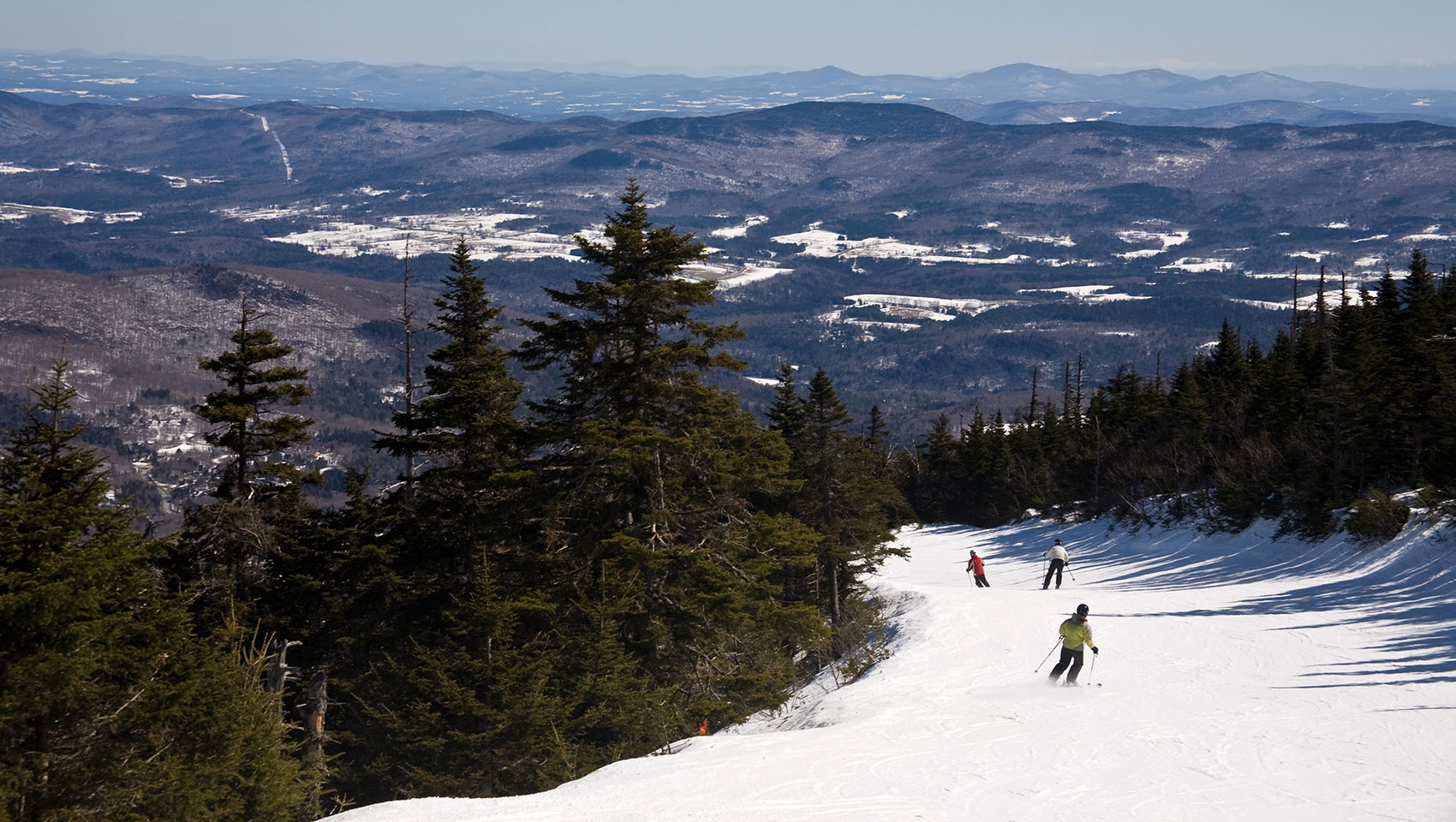 skiers going down a slope with more mountains in the background