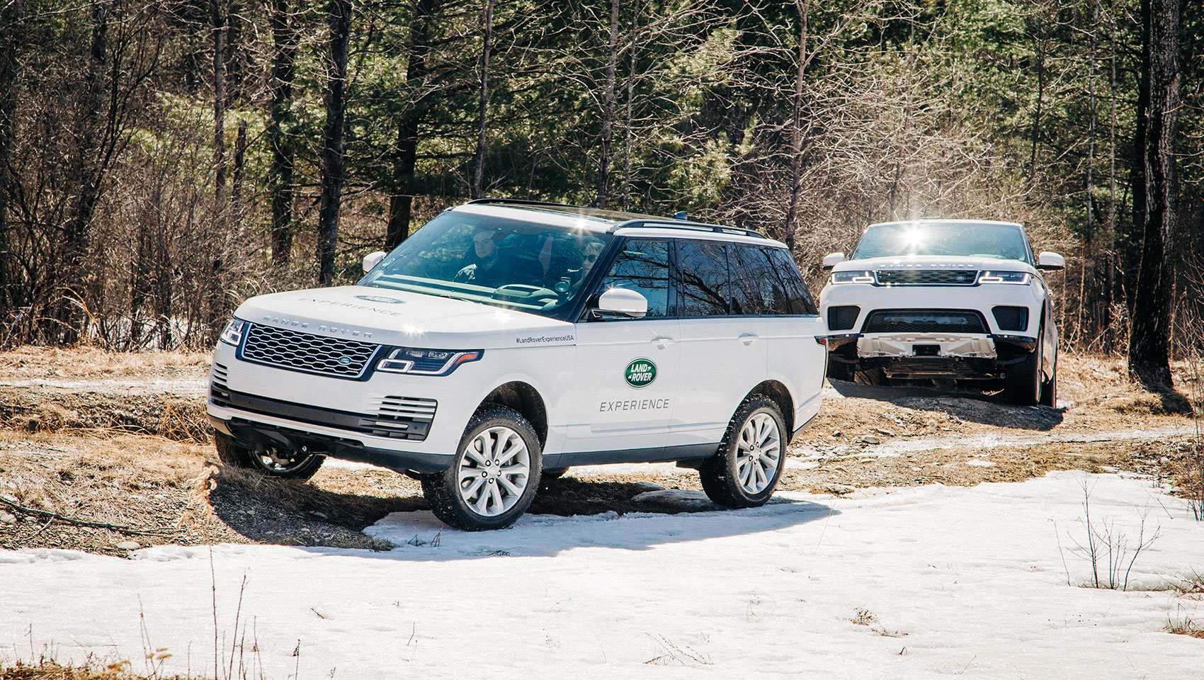 Land Rover experience in Vermont with 2 Land Rovers driving through a wooded area