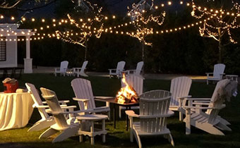 Lounge chairs around a firepit under string lights -  Fire Pits