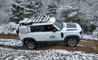 Land Rover Defender 110 drving on a muddy trail in snow